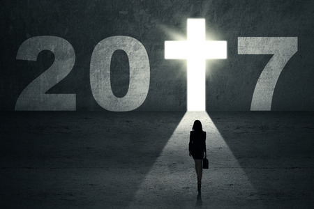 way: New Year 2017 is coming concept. Silhouette of a businesswoman looking at a cross symbol shaped a doorway with number 2017