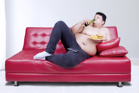 slob: Image of lazy fat man reclining on couch while drinking fresh beer and eating junk food