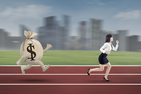 downgrade: Young entrepreneur escaping from a bag of dollar while running  on the track