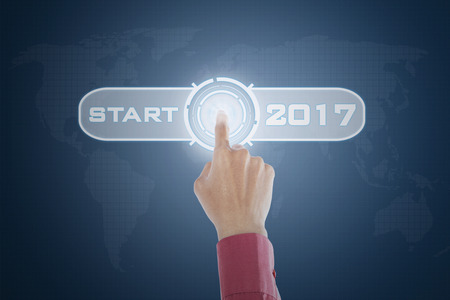 beginning: Close up of businessperson hand touching a virtual start button with number 2017 on the futuristic interface