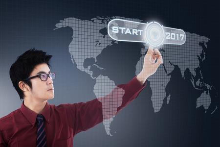 mapa de china: Foto de un joven empresario chino tocando un botón de inicio con los números 2017 y mapa del mundo en la pantalla virtual