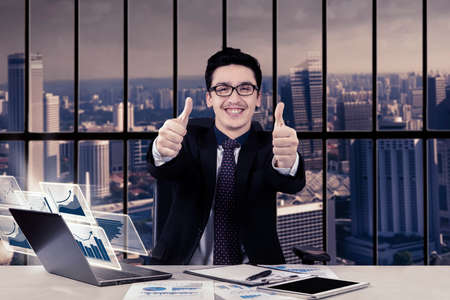 working on computer: Image of Arabian entrepreneur showing two thumbs and using computer while sitting in the office Stock Photo