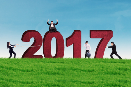 young entrepreneurs: Group of young entrepreneurs with numbers 2017 on the meadow. Concept of business and new year