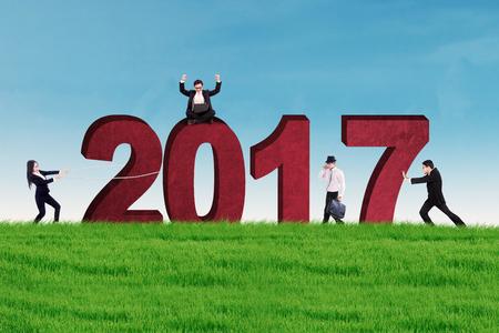 jovenes empresarios: Grupo de jóvenes empresarios con los números de 2017, por el prado. Concepto de negocio y el año nuevo Foto de archivo