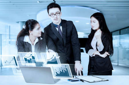 debating: Image of business people standing and debating in a business meeting while pointing at the laptop with problem report of finance Stock Photo