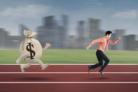 chased: Young entrepreneur is being chased by a bag of dollar on the track