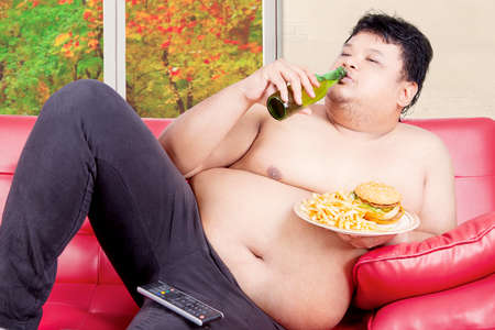potbelly: Young overweight man reclining on couch while drinking and eating junk food with autumn background on the window