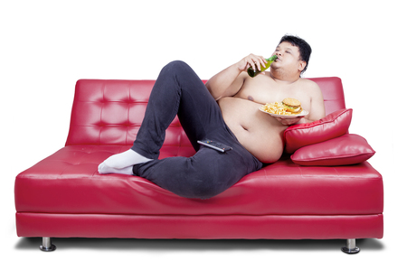 couch: Overweight man reclining on couch and holding junk food while drinking fresh beer  with watching tv, isolated on white the background