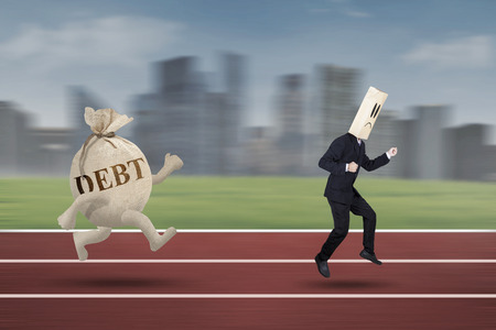 Anonymous entrepreneur running on the track while escaping from debt Stock Photo