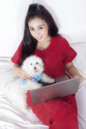 bedstead: Portrait of beautiful woman and maltese dog lying on the bed while using laptop Stock Photo