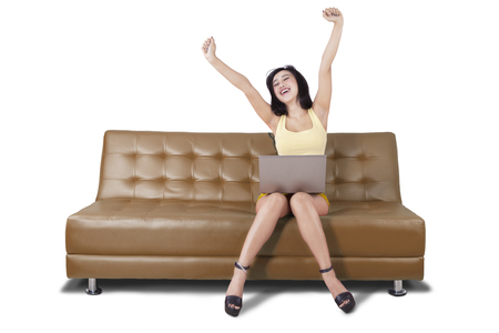 excited woman: Image of attractive woman using laptop while raising hand and sitting on the brown couch Stock Photo