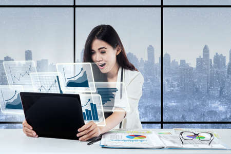 winter window: Young businesswoman sitting and looking virtual chart screen while holding laptop with winter background on the window Stock Photo