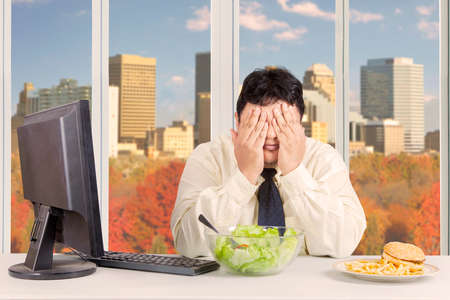 temptation: Overweight entrepreneur trying to diet while refusing temptation of food with autumn background on the window