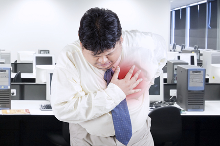 Portrait of businessman with overweight having heart attack in the office Imagens