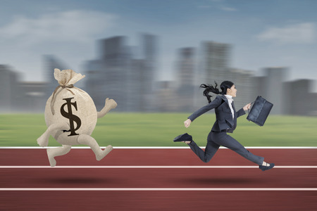 downgrade: Businesswoman running with bring briefcase on the track while escaping from a bag of dollar Stock Photo