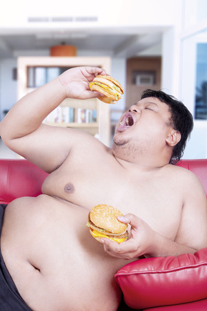 potbelly: Image of a fat man holding two burgers while sitting on the red sofa at home Stock Photo