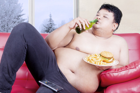 slob: Image of an overweight man sitting on the red couch while drinking beer and eating junk food