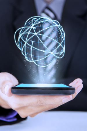 Close up of businessman holding cellphone with 3d globe with connection network Stock Photo