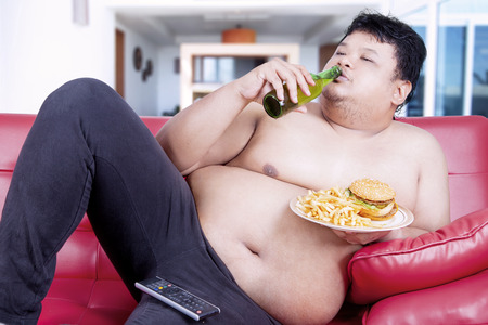 unattractive: Unattractive overweight man sitting on the red sofa while drinking beer and eating junk food in front of tv at living room Stock Photo