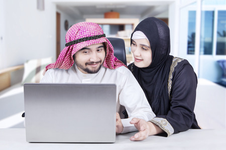 Muslim couple talking and sitting together in the living room while using laptop with happy expression Stock Photo