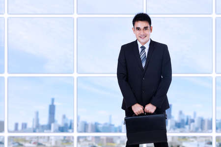 employees: Portrait of young businessman standing in the office with a briefcase