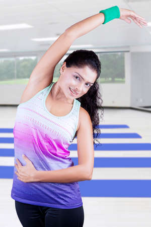 center position: Beautiful Indian woman workout at gym while wearing sportswear and smiling at the camera