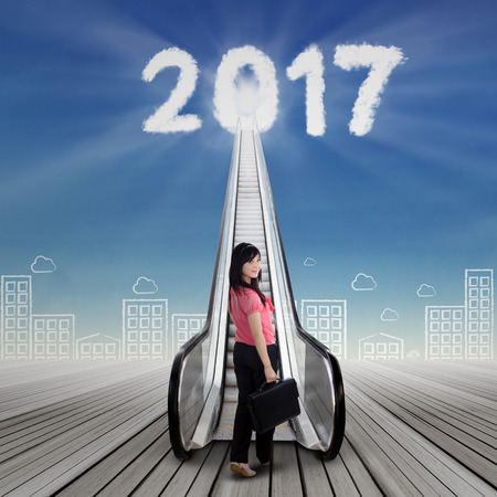 Beautiful woman holding suitcase and looking at the camera while climbing upward a stair to the future with bright numbers 2017 on cloudscape