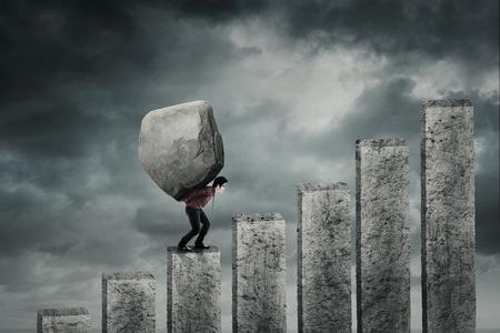 Jonge zakenman die op de financiële grafiek loopt tijdens het dragen van een grote steen. Concept van hard werk