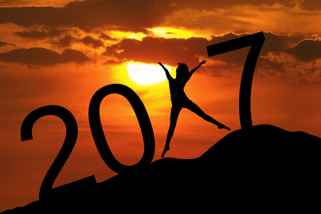 Silhouette young woman jumping on the hill and 2017 years while celebrating new year, 2017