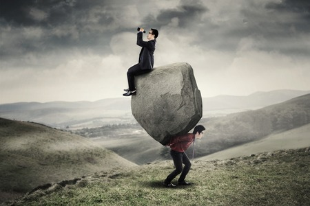 Young businessman looking through binoculars and sitting on the stone while his partner carrying the stone on the hill