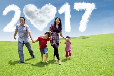 Photo of joyful Asian family running on the meadow with cloud shaped numbers 2017