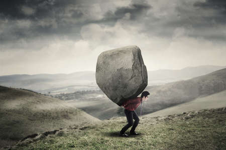 financial burden: Young businessman walking on the hill while carrying a big rock. Concept of business adversity