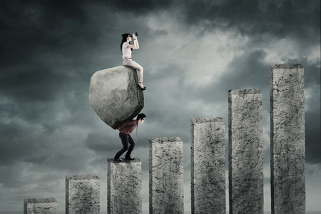 lifting: Image of a male Asian businessman carrying a big stone and climbing a chart while his partner sitting on the stone Stock Photo