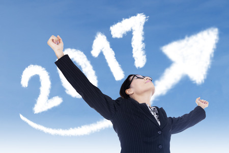 year increase: Portrait of successful woman outstretched hands under upward arrow and numbers 2017 Stock Photo