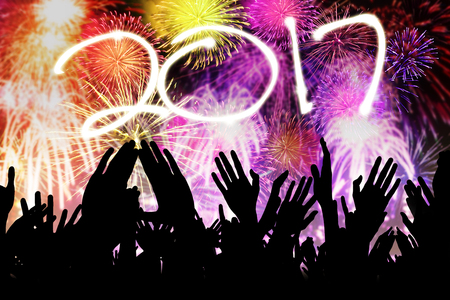 end of year: Silhouette of crowd hands people celebrating new year 2017 while watching fireworks together in the end year party Stock Photo