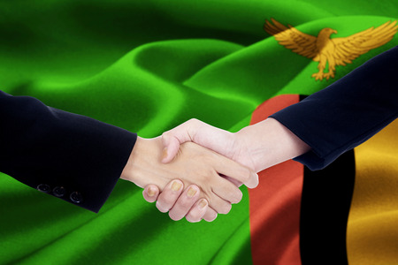 Portrait of business team handshake with two entrepreneur hands in front of Zambia flag