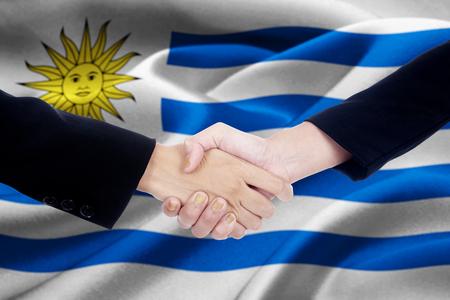 bandera de uruguay: Foto de un apretón de manos empresarios converse con las dos manos del trabajador frente a la bandera Uruguay ondeando en el viento