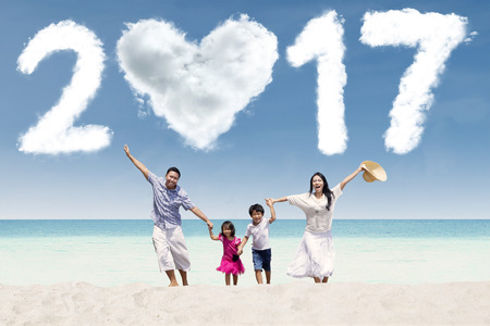 celebrate year: Cheerful Asian family running on the beach while holding hands with numbers 2017 on the sky