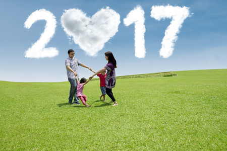 celebrate year: Joyful Asian family playing on the meadow while celebrate new year day with cloud shaped numbers 2017 on the sky