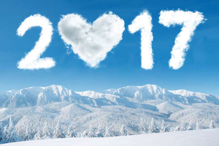 Image of cloud shaped numbers 2017 and heart symbol on the sky above snowy mountain.