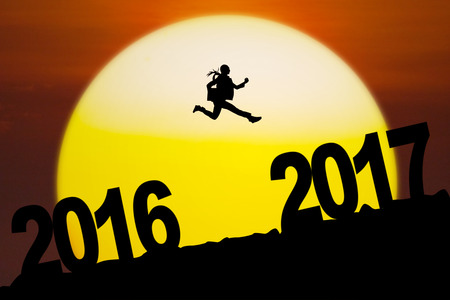Silhouette of young entrepreneur holding document while leaping between 2016 to 2017 years with sundown