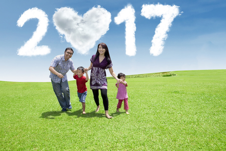 celebrate year: Cheerful Asian family running at field while holding hands together with cloud shaped numbers 2017