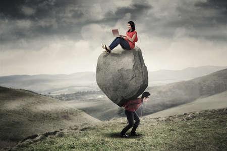 trabajando duro: empresaria asiática que se sienta en la piedra y equipo portátil mientras que su compañero que lleva la piedra en la colina Foto de archivo