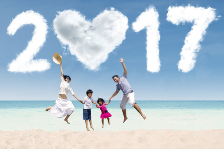 celebrate year: Happy Asian family jumping together on the beach while holding hands with cloud shaped numbers 2017 Stock Photo