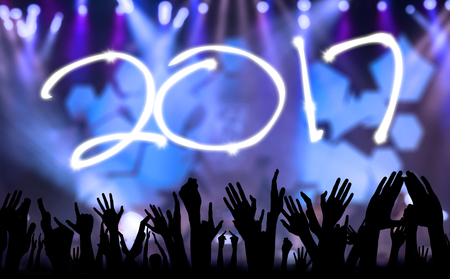 Portrait of number 2017 with silhouette hands people while celebrating new year in the party Stock Photo
