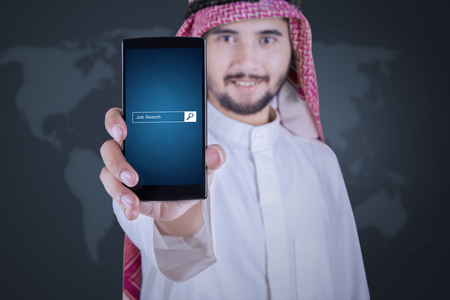 seeker: Image of Arabian businessman displaying a mobile phone with job search bar on the screen