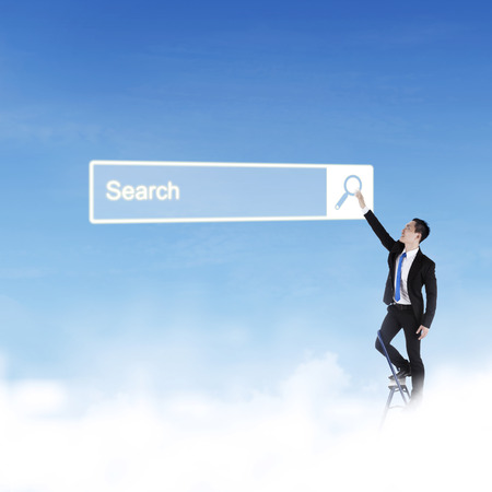 Young Asian businessman standing on the stairs and pressing a virtual search bar on the blue sky