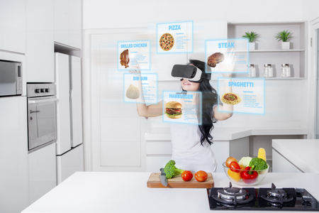 Young woman cooking in the kitchen while wearing virtual reality glasses to find menu or recipe on futuristic screen