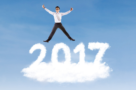 Image of young businessman leaping above cloud shaped number 2017 on the blue sky