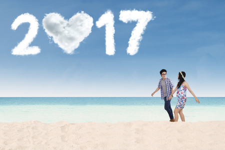 holding hands while walking: Happy Asian couple walking on the beach while holding hands with cloud shaped number 2017